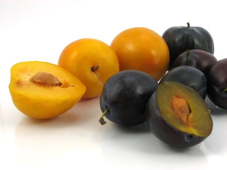 yellow and red plum with seed on white backgound
