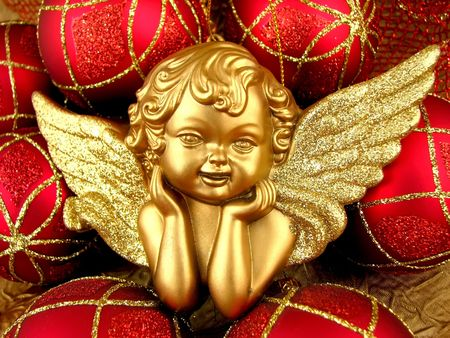 Gold Angel and red bulbs on Christmas Time Stock Photo