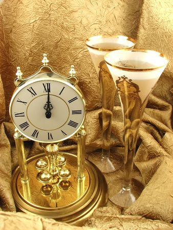 clock and two glasses of champagne on the golden background Stock Photo - 2095925