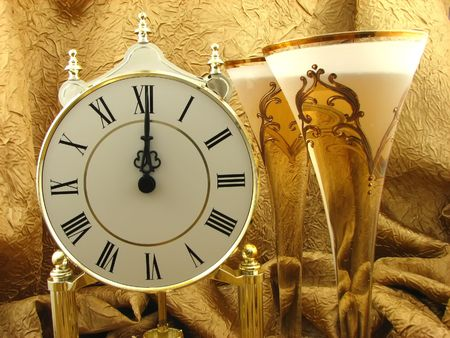clock and two glasses of champagne on the golden background