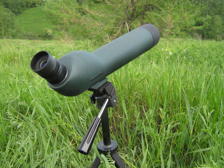 Telescope on a stand on a background of green grass. Green grass.