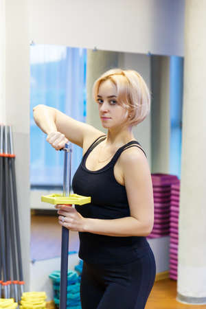 A young woman holding a bar, preparing to engage in fitness in the gym. He looks at the camera and configured to perform sports exercise.