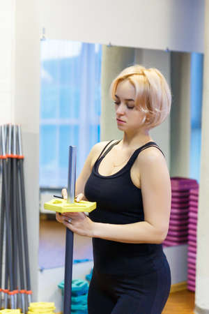 A young woman holding a bar, preparing to engage in fitness in the gym. He looks at the bar and adjusted to perform sports exercise. 写真素材