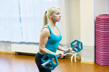 A young woman holds a barbell in her hands and lifts it in front of her. The girl is engaged in fitness in the gym.