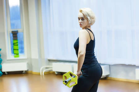 Blonde girl engaged in sports and fitness in the gym on the background of a large window. Raises the bar with his back to the camera.