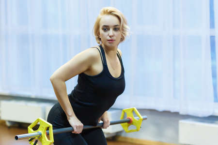Blonde girl engaged in sports and fitness in the gym on the background of a large window. Raises the bar and looks at the camera.