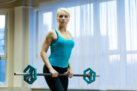 Athlete engaged in fitness in the gym on the background of a large window. Raises the bar facing the camera.