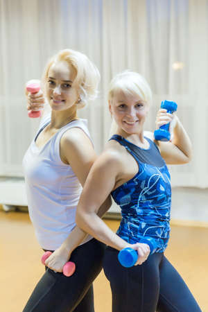 Two blonde girls with dumbbells stand back to back and smile