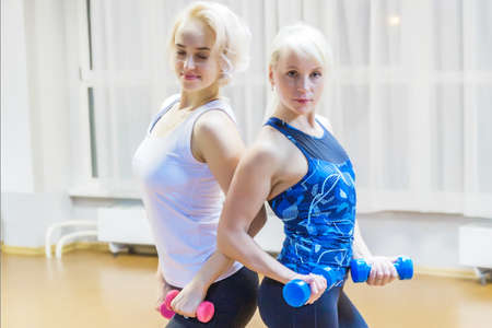 Two blonde girls with dumbbells stand back to back 写真素材