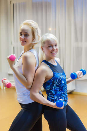 Two blonde female athletes are with dumbbells and smiling 写真素材