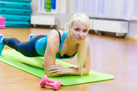 A young girl doing fitness on the Mat. Looking at the camera. 写真素材