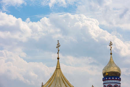 The concept of faith in God: Orthodox cross against the sky with clouds.