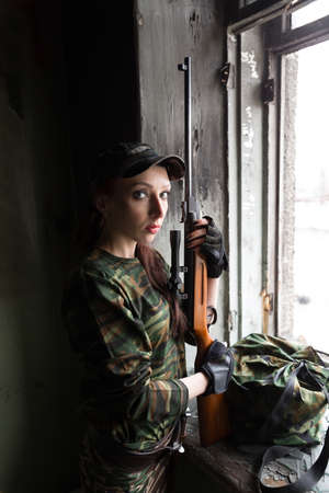 The girl portrays a soldier sniper. The girl is holding a sniper rifle. Reklamní fotografie