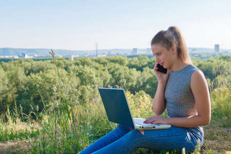 The girl is talking on a smartphone and looking at the laptop monitor. Girl in jeans in nature with a laptop. Reklamní fotografie