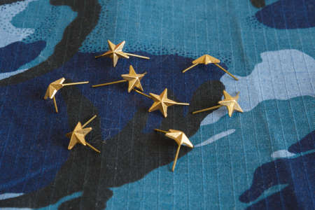 Gold stars for shoulder straps on blue camouflage fabric. Military emblems of Russian troops and services. No people. Photo Banco de Imagens
