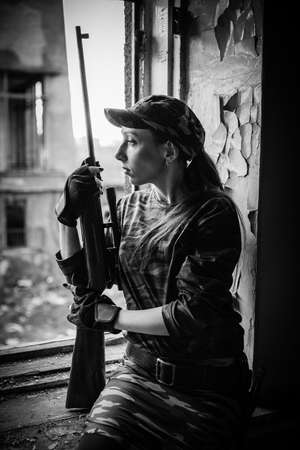 A young woman with a rifle in uniform at the window looking at the street. Female sniper in camouflage and cap. Reklamní fotografie