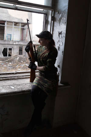 A young woman with a rifle at the window looking at the street. The woman sniper in a green suit and cap.