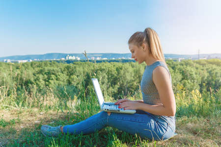 Girl with laptop on the nature on the background of forest and sky. The concept of combining leisure and work. Individual entrepreneur.