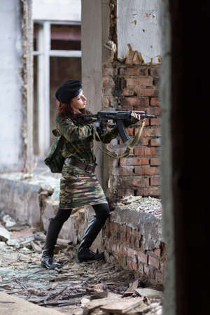 A young woman in an abandoned building with a gun. Laser sight on the machine. Aiming from the machine with a laser.