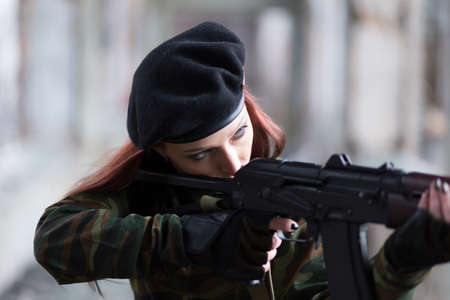 A young girl with a green camouflage uniform and a black beret with a gun among the ruins. Stock Photo