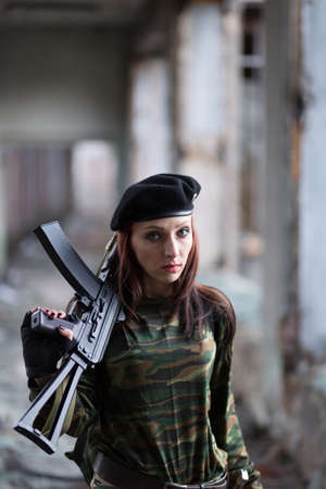 A young girl with a green camouflage uniform and a black beret with a gun among the ruins. Girl warrior with weapons.