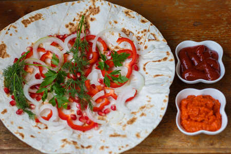 Red bell peppers, onions, pomegranate and parsley on lavash for roasted meat, sausages or sausages are served with ketchup and Armenian snack Aivar. The view from the top.