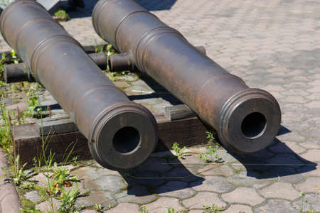 Old guns on wheels in 1812. Artillery fortress guns on wheels. The barrels of artillery guns.