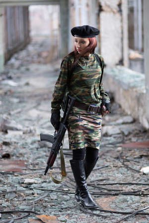 Soldier girl with weapons in camouflage uniform in a destroyed building. The concept of service in the army Фото со стока