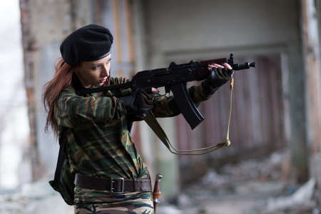 Soldier girl with weapons in camouflage uniform in a destroyed building. The concept of service in the army