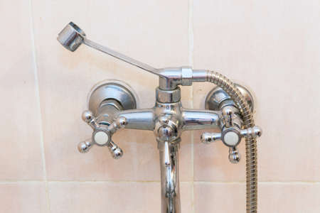 Old faucet the faucet Assembly in the bathroom. Limescale on chrome taps and mixer shower