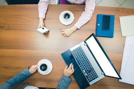 Pausa caffè alla scrivania in ufficio. Mani di giovani ragazze sul desktop con un laptop e uno smartphone. La vista dall'alto. Archivio Fotografico
