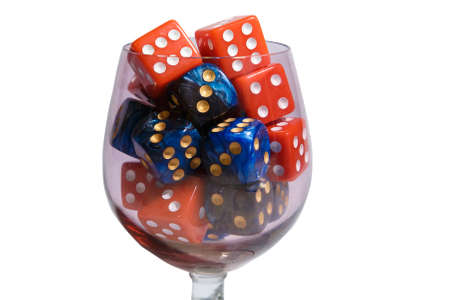 Red and blue dice in a glass. Many dice of different colors in a glass glass.