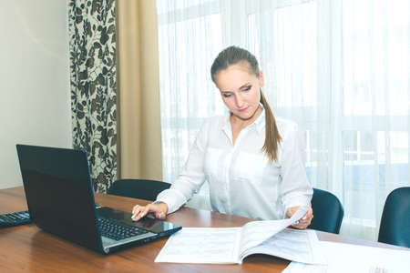 The girl in the workplace in the office with a laptop. Laptop with white blank screen.