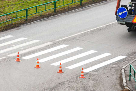 The road service updates the pedestrian crossing on the highway with paint. Prohibiting chips before a pedestrian crossing