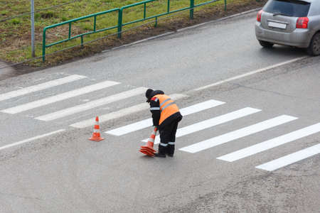 The road service updates the pedestrian crossing on the highway with paint. The employee puts forbidding chips on the road.