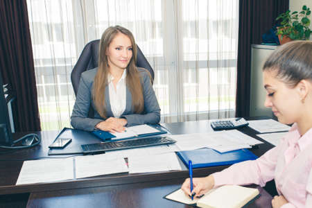 A woman leader and her secretary at the table plan and write down a work plan for the day. Office work concept.