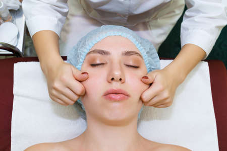 The masseur cosmetologist conducts a procedure for rejuvenating the skin of the face using manual massage. top view close up
