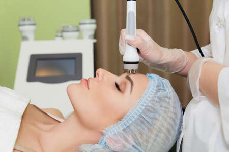 A young woman is lying on the RF-lifting procedure for face skin tightening and face contour correction. Close-up.
