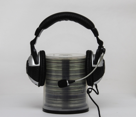Earphones with a microphone are dressed on the container with the disks CD, DVD photo