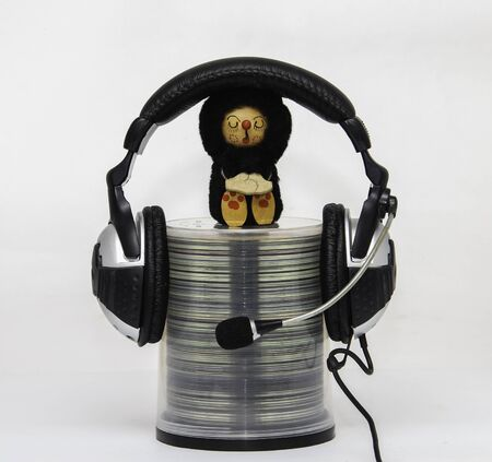 The container with disks on which earphones are put on and the doll as though listening to records sits  photo