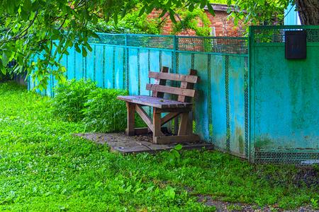Wooden bench near a fence. Standard-Bild