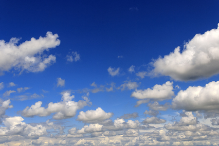 The blue sky turning into blue with white cumulus clouds on the parties of a shot. Below they are extended by a dense chain.
