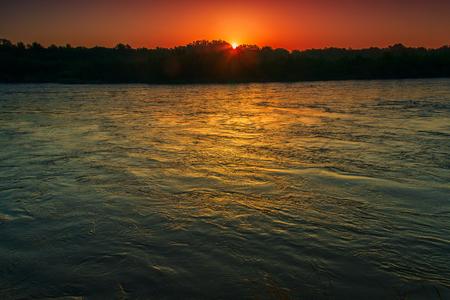 Waters of the fast river in twilight slightly podsvenny beams just beginning sunrise. Kuban, Krasnodar Krai.