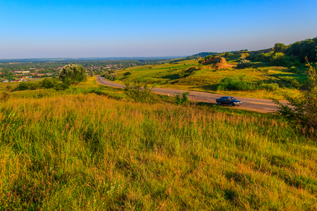 The road with cars conducting down with the hill, and also the open area where hills are covered with a grass and separate trees. Stock Photo