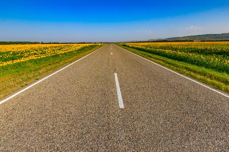 La carretera a través de campos con cultivos es visible lejos, hacia el horizonte.