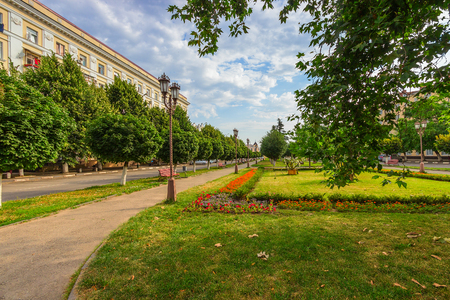 Landscaping of the square in the city with lamps, benches and paths for walks. The main covering is a lawn grass, is framed with bright strips of flowers. Stock Photo