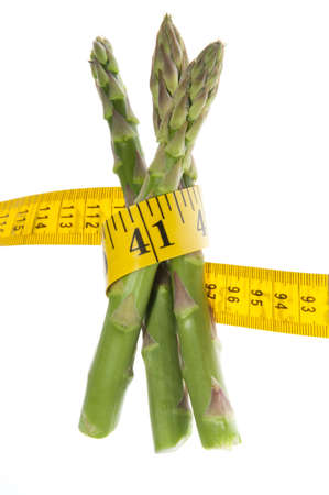 healthy path: Healthy green fresh raw asparagus wrapped around a yellow tape measure to symbolize a healthy diet, lifestyle or weight loss. Studio isolated on a white background with a clipping path.