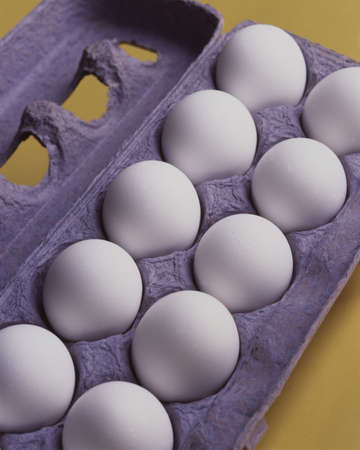 Dozen eggs in a blue carton on a yellow background. photo