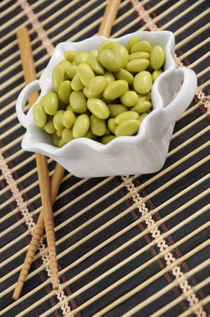 placemat: Soybeans in a white dish with chopsticks on a bamboo placemat.