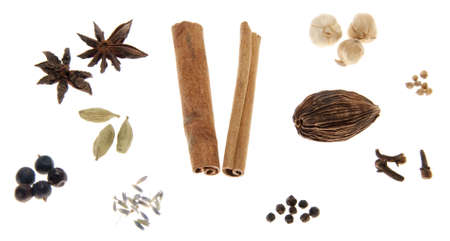 A variety of whole spices isolated on a white background. Spices include : cinnamon, star anise, cloves, coriander, sichuan peppercorns, juniper berries, cardamom, allspice, lavender flower & black cardamom.
